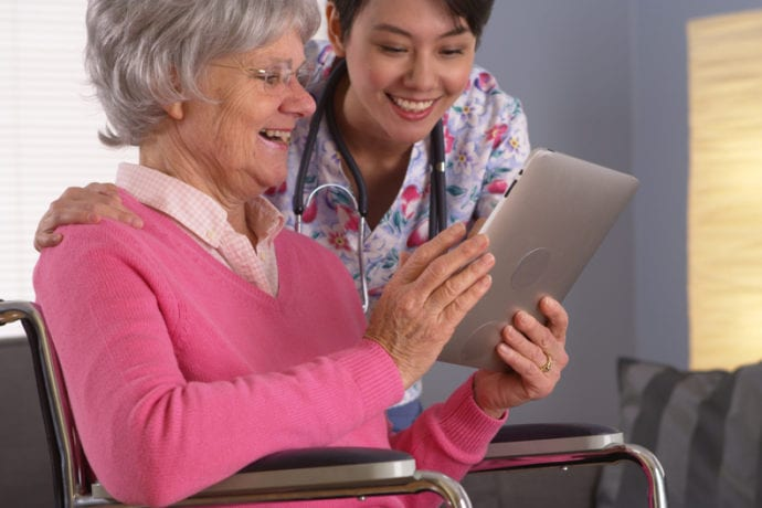 Elderly patient and Asian nurse having fun with tablet