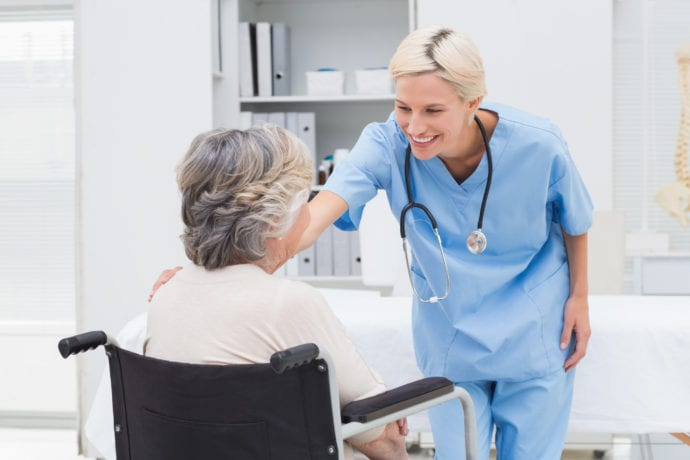 Nurse consoling patient sitting on wheelchair